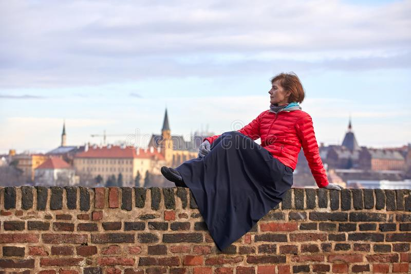 praga Una mujer joven en una chaqueta roja se sienta en una pared de ladrillo y admira la vista de la parte histórica de la ciuda imagenes de archivo