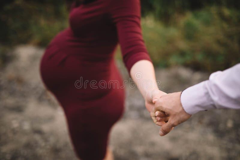 Pragnant妇女接触她的丈夫,步行本质上 免版税图库摄影