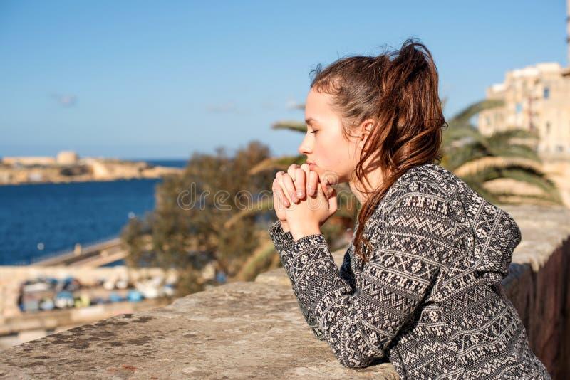 Pragnienie dziewczyny pozycja i modlenie robimy życzeniu blisko parapet nad wodą morską na jaskrawym słonecznym dniu obraz stock