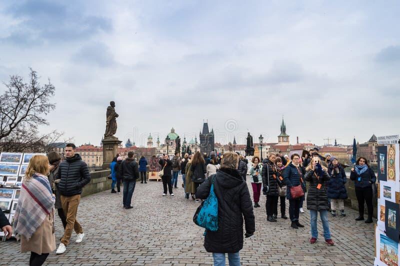 Prague Bohemia/Tjeckien - November 2017: Turister som mest går på den berömda Charles Bridge Karluv på regnig höstdag royaltyfria foton
