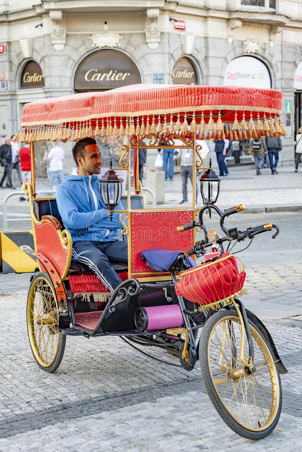 "Man on a tricycle in Prague. Prague, capital city of the Czech Republic, is bisected by the Vltava River. Nicknamed ""the City of a Hundred Spires,"" royalty free stock photography"