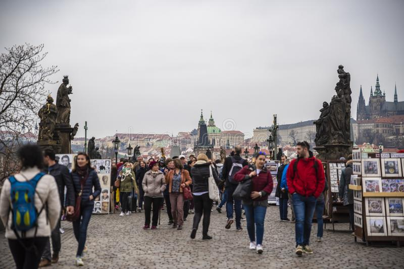 "People on Charles Bridge in Prague. Prague, capital city of the Czech Republic, is bisected by the Vltava River. Nicknamed ""the City of a Hundred Spires stock image"