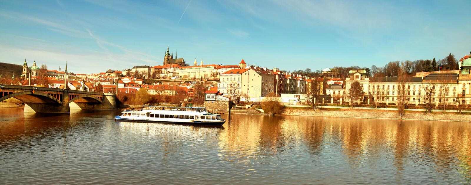 Prague cityscape in golden light in Autumn. View on St. Vitus Cathedral and Prague Castle across Vltava river with passenger ship. Cityscape of Prague on golden royalty free stock photo