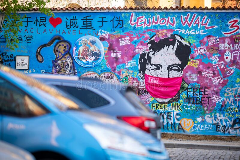 PRAGUE, CZECH REPUBLIC - APRIL 17: The face of John Lenon on the famous Lenon wall in Prague is covered with a pink face mask royalty free stock images