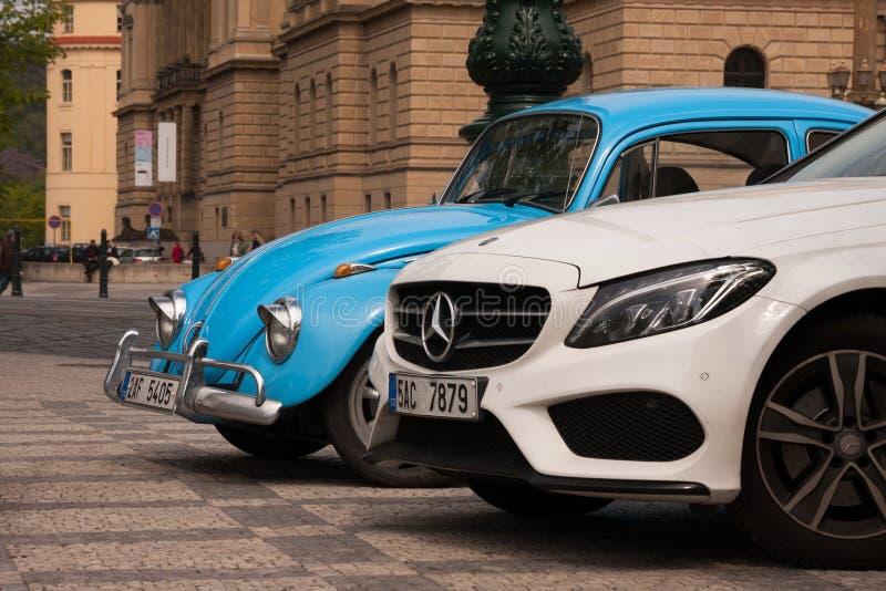 PRAGUE, CZECH REPUBLIC - APRIL 21, 2017: A small blue vintage Volkswagen Beetle car next to a big white Mercedes. Parked in front of the Rudolfinum concert stock photo