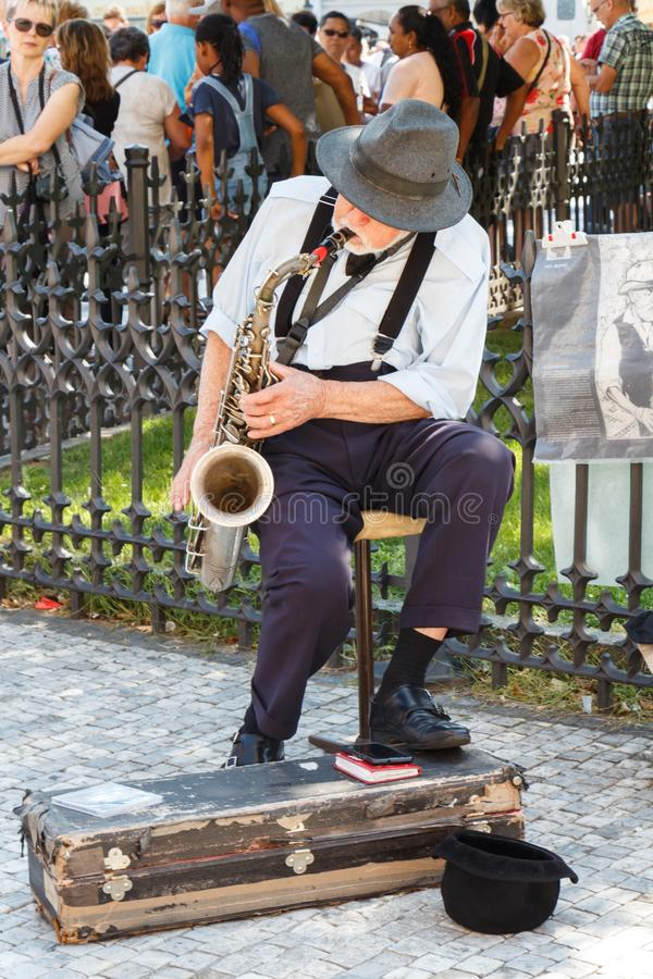 PRAGUE - CZECH REPUBLIC, AUGUST 14 : Old man playing saxophone in a street, August 14, 2017 stock photo