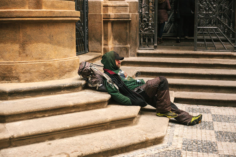 Prague, Czech Republic December 24, 2016 - Homeless hungry poor man sitting on the sidewalk in the city center. Unhappy stock photography
