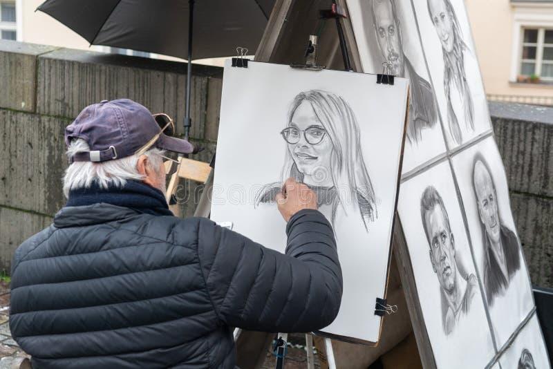 Prague, Czech Republic - December 2018: A street artist painting a portrait from the photograph on the Charles bridge.  stock photo