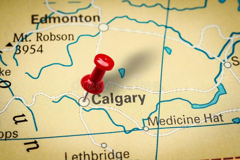 Pushpin pointing at Calgary city in Canada. PRAGUE, CZECH REPUBLIC - JANUARY 12, 2019: Red thumbtack in a map. Pushpin pointing at Calgary city in Canada royalty free stock image