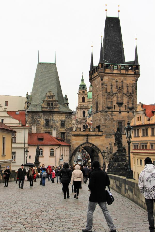 Prague, Czech Republic, January 2015. The tower and gate at the end of the Charles Bridge and numerous tourists in the city. Magnificent Gothic architecture stock photos