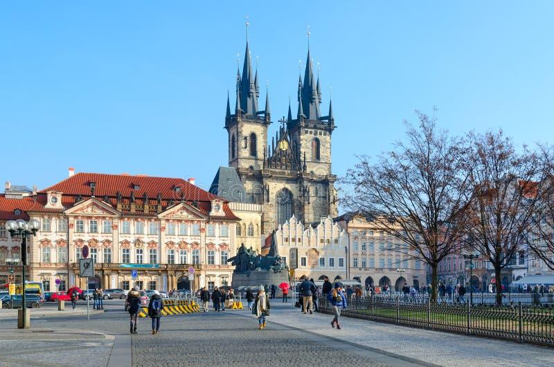 Tourists walk along Old Town Square, Prague, Czech Republic. Tyn Church, monument to Jan Hus royalty free stock image