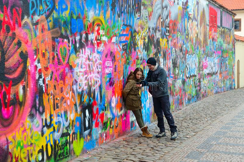 Young people are photographed at famous wall of John Lennon in Prague, Czech Republic royalty free stock images