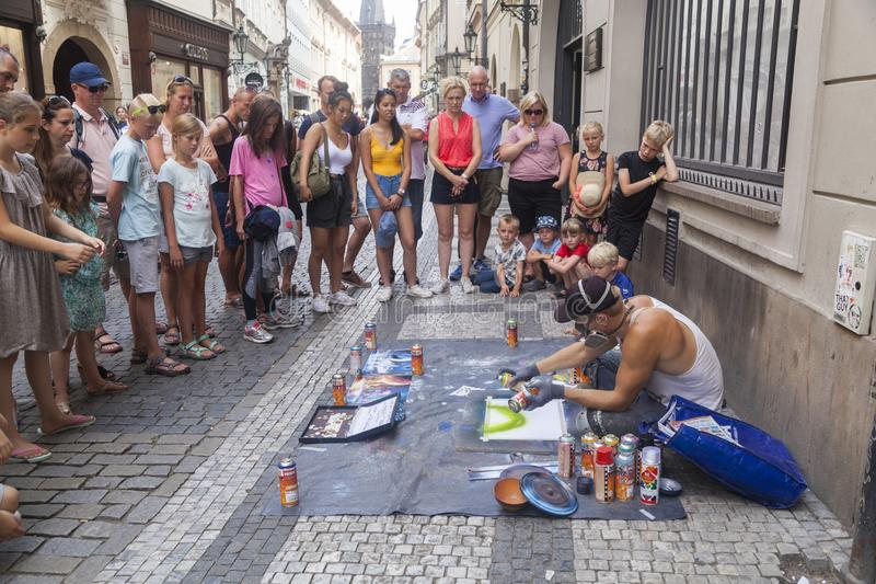 Street artist. Prague, Czech Republic - July 16 2018: A street artist painting with spray colors and people watching him stock photography