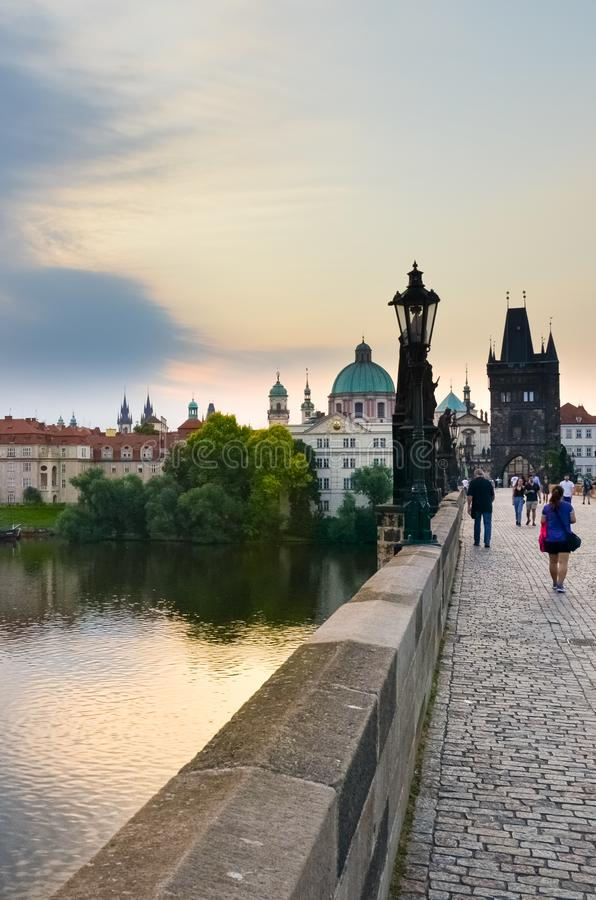 Prague, Czech Republic - June 27th 2019: People walking on historical Charles Bridge in the early morning. Sunrise light. Famous stock photography
