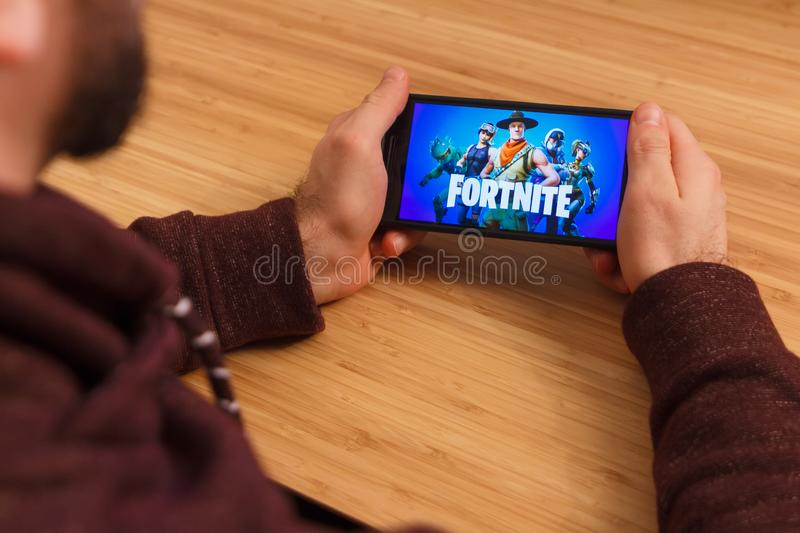 PRAGUE, CZECH REPUBLIC - MARCH 16, 2019: Man holding a smartphone and playng the Fortnite mobile game. An illustrative stock photography