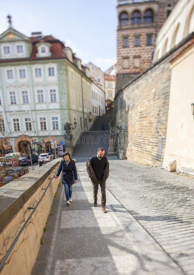 Prague, Czech Republic - March 15 2017: Young Couple Walking Along Urban Street A special lens was used to tilt the optical axis royalty free stock images