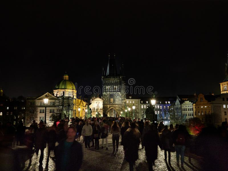 Prague, Czech Republic - Nov 02, 2018 People are corssing Saint Charles Bridge at night. View towards Prague Old Town royalty free stock photography