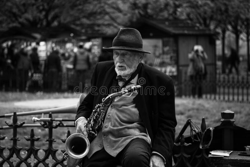 Prague, Czech Republic/ 1 November 2019: Black and white portrait of old man, street musician playing sax. Tourist attraction. Dramatic portrait royalty free stock image
