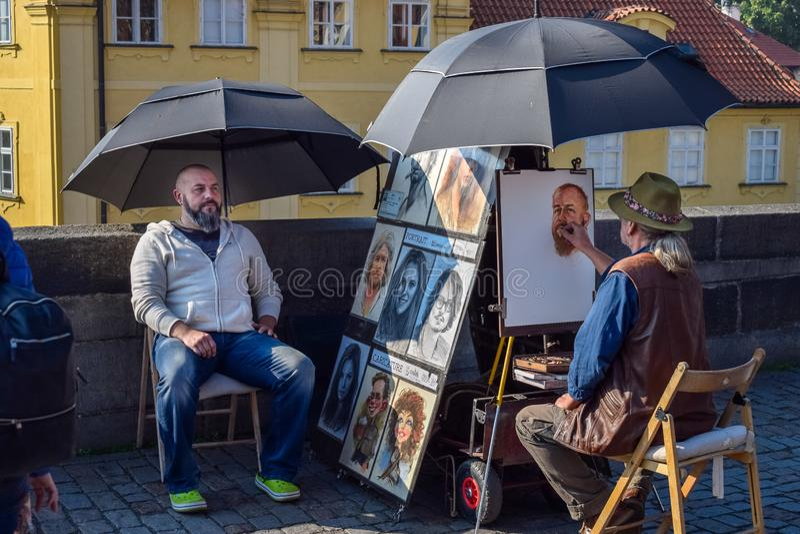 PRAGUE, CZECH REPUBLIC - OKTOBER 10, 2018: Street artist paints a portrait of man under umbrella on bridge stock photos