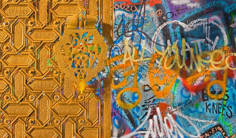 PRAGUE, CZECH REPUBLIC - SEPTEMBER 11, 2010: Detail of John Lennon Peace Wall created in 1980 and the gate of Cathedral of Seville royalty free stock image
