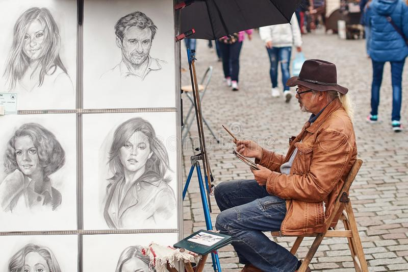 Prague, Czech Republic - September 27, 2014: Street portrait painter and examples of his art drawn with pencil. Prague, Czech Republic - September 27, 2014 stock photos