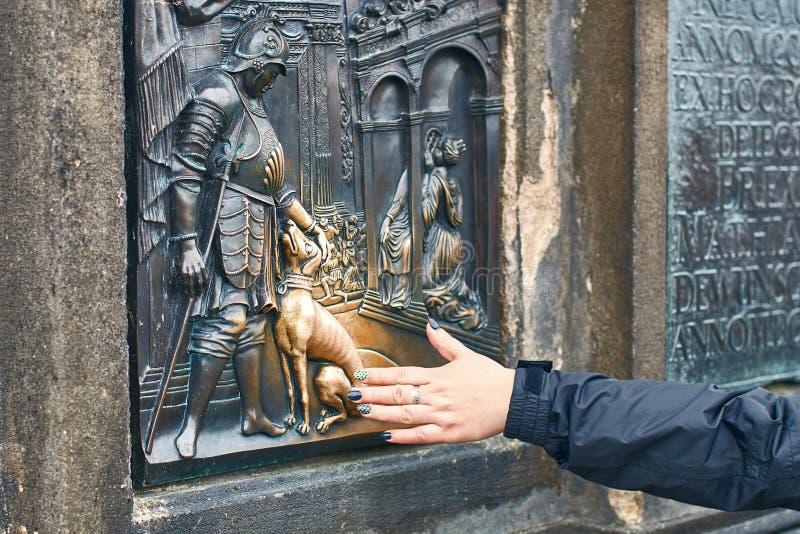 Prague, Czech Republic - September 27, 2014: Tourist is rubbing a bronze plaque of Saint John Nepomuk`s dog part of the stock photo