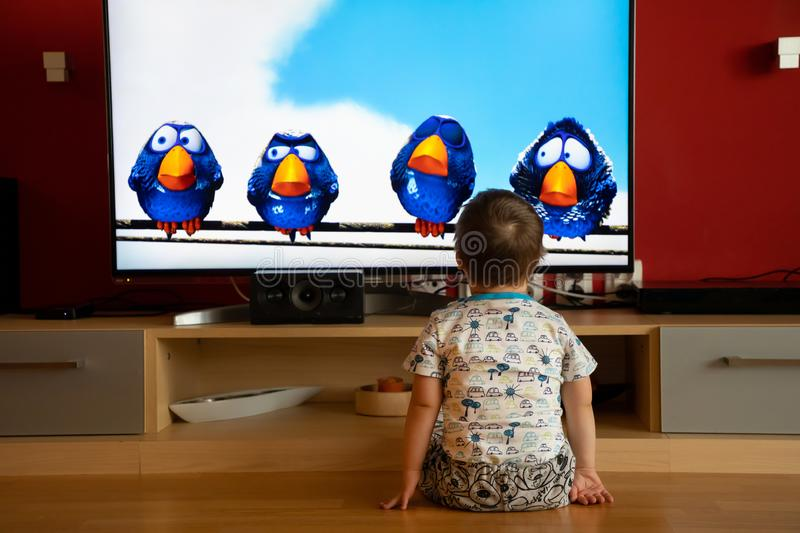 Prague, Czech Republic -18.03.2019: Small boy with Down syndrome watching cartoon. On TV stock image