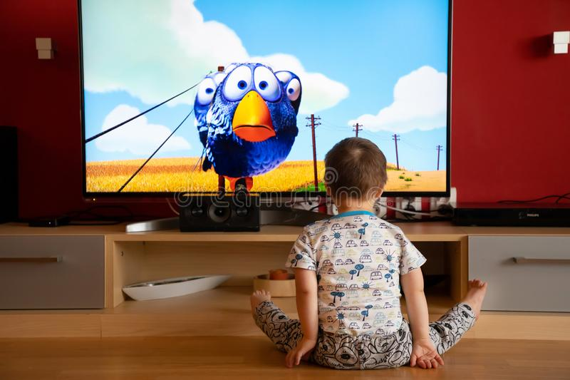 Prague, Czech Republic -18.03.2019: Small boy with Down syndrome watching cartoon. On TV royalty free stock images