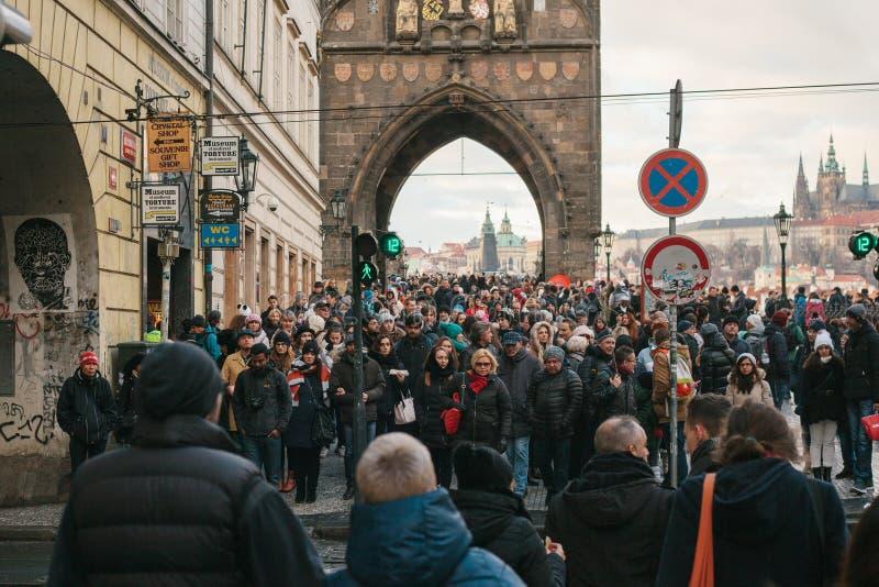 Prague December 24, 2016: En folkmassa av lokaler och turister korsar vägen till klartecknet bredvid Charles Bridge arkivbilder