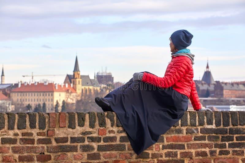 Prague En ung kvinna i ett rött omslag sitter på en tegelstenvägg och beundrar sikten av den historiska delen av staden av Prague arkivbild