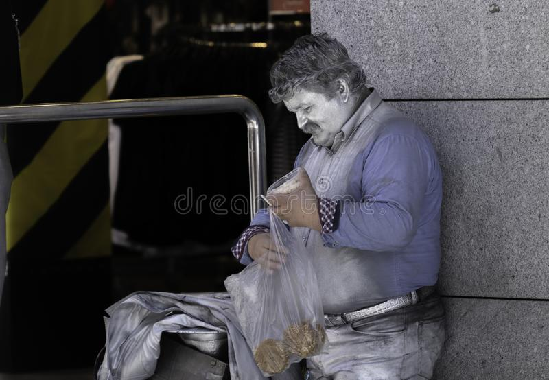 Prague Europe male Street performer dressed in silver paint having a lunch break from the job for tourists stock photography