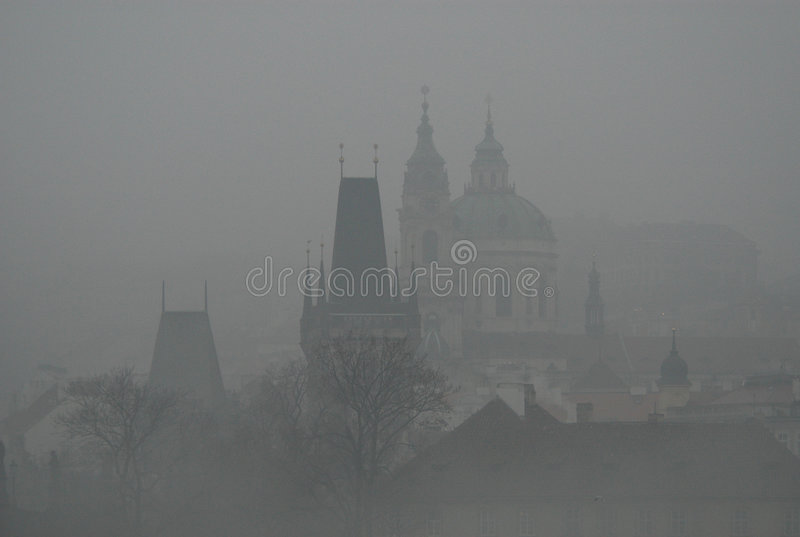 Prague in the Fog-grain visible. The Gothic towers of the Charles Bridge and the dome of the Baroque church of St. Nicholas on the Lesser Town in Prague, Czech royalty free stock images