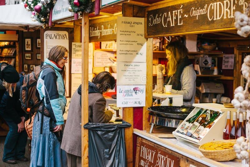 Prague, le 15 décembre 2016 : Le vendeur offre à des clients un large choix de miel et de divers vins Boutique de Noël photo libre de droits