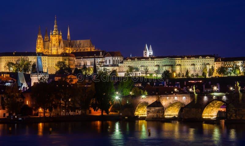 Prague lumineux à l'heure crépusculaire avec un ciel bleu sans nuages se reflétant en rivière de Vltava - vue au château et au Th photographie stock libre de droits
