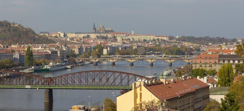 Prague - panoraman av staden med broarna och Castelen i backgrounen från Vysehrad fotografering för bildbyråer