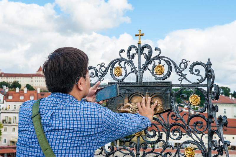 Prague, République Tchèque 13 août 2017 : équipez toucher la statue de St John Nepomuk sur le pont de Charles Contact du prêtre s photographie stock libre de droits