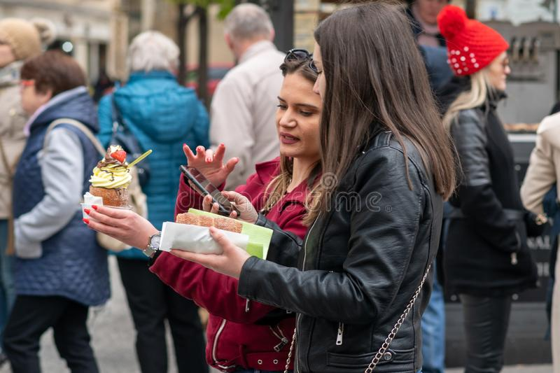 PRAGUE, RÉPUBLIQUE TCHÈQUE - 12 AVRIL 2019 : Les touristes féminins mangent de la nourriture du marché pendant les festivités de  photos stock