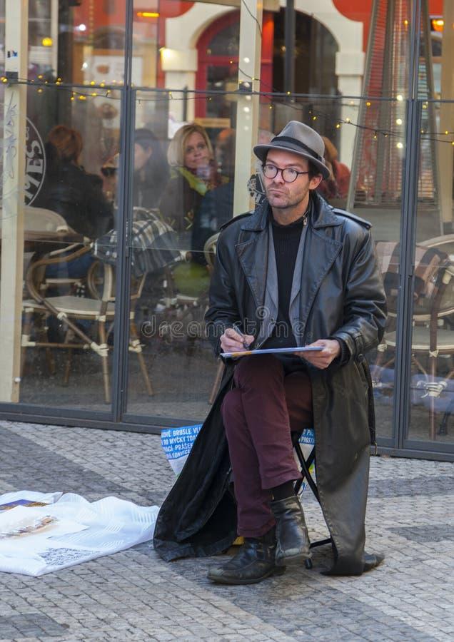 Prague, République Tchèque - 15 mars 2017 : un artiste masculin dessine un croquis tout en se reposant sur la rue photo libre de droits