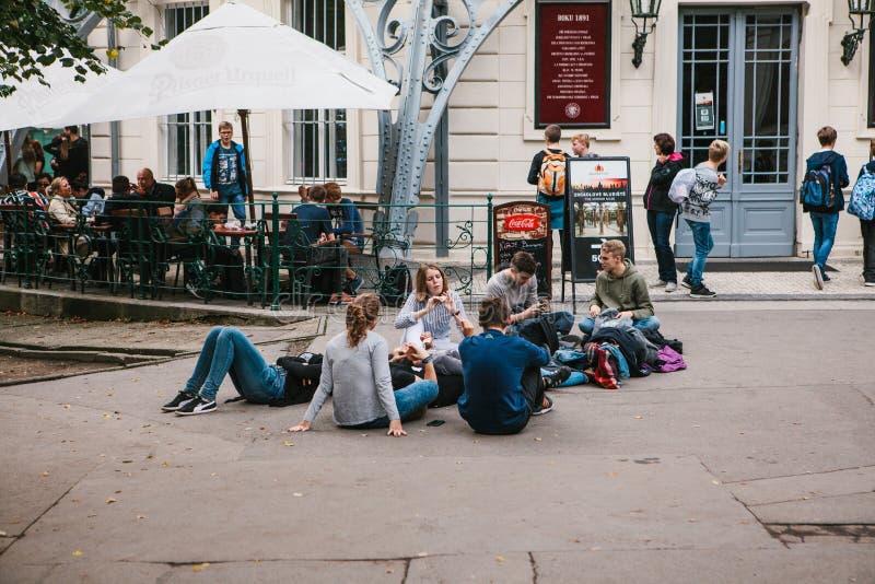 Prague September 25, 2017: En grupp av unga vänner av studenter ligger och sitter på jordningen och meddelar med varje royaltyfri bild