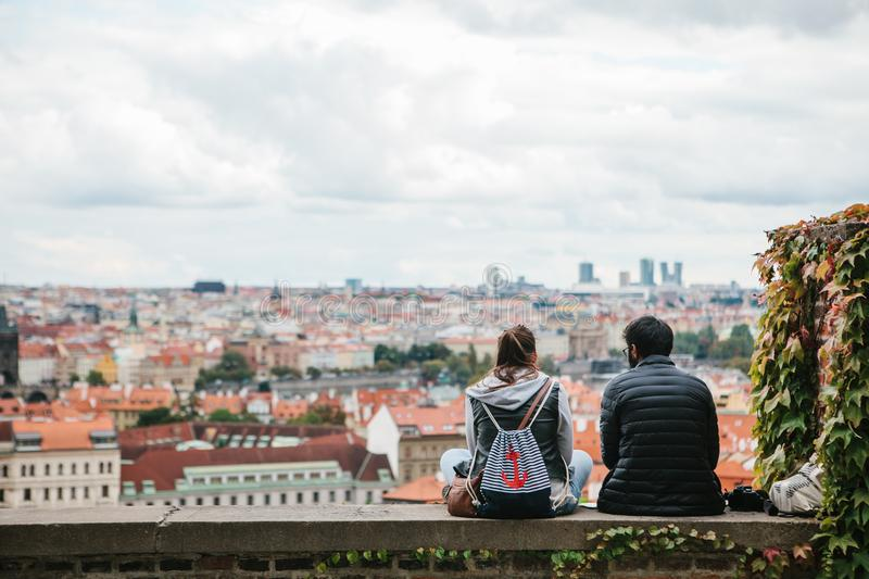 Prague, September 18, 2017: Young couple in love or friends are sitting and admiring the beautiful architecture of the royalty free stock images