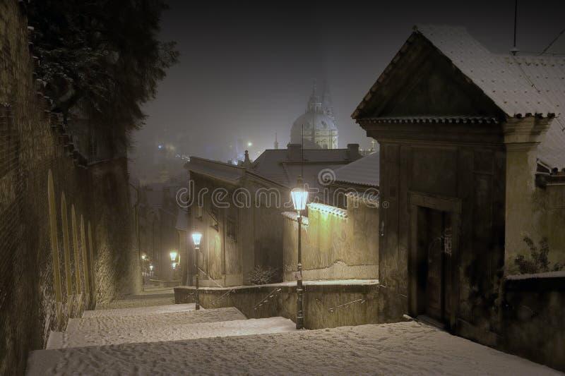 Prague slotttrappa som leder till den gammala townen av Prague i vinternatt arkivbild