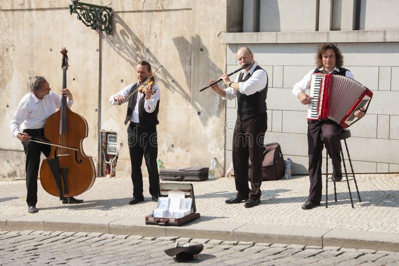 Prague Tjeckien - April 19, 2011: Kvartett av musiker som spelar musikinstrument för turister på gatan i Prague royaltyfria foton