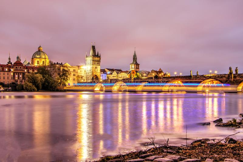 Prague Tjeckien, April 22, 2019 - sikt av aftonen Charles Bridge Skymning på Vltavaen i Prague royaltyfria bilder