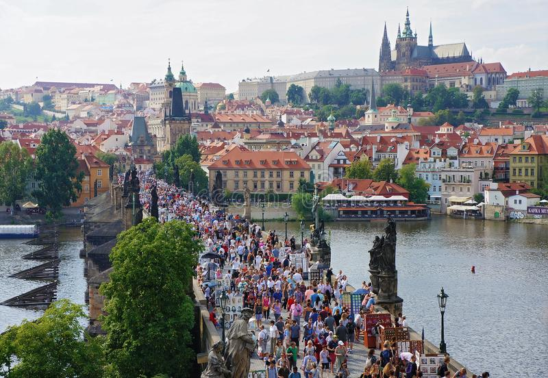Prague Tjeckien - Augusti 14, 2016: Folkmassor av folk går på Charles Bridge - en populär turist- gränsmärke Prague townscape arkivfoton
