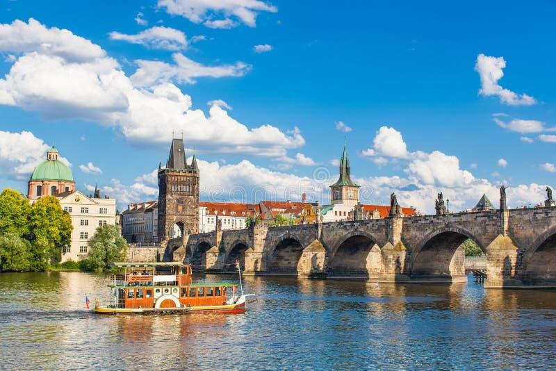 Prague Tjeckien, Charles Bridge över den Vltava floden som skeppet seglar på royaltyfri fotografi