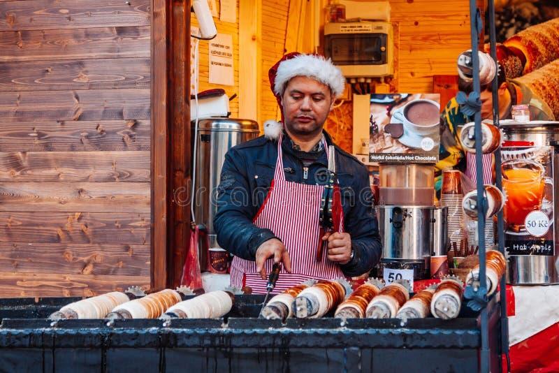 PRAGUE TJECKIEN - DECEMBER 23, 2015: Trdelnik är gatamat av Prague Trdlo är rör av söt deg som lagas mat på ett öppet f fotografering för bildbyråer