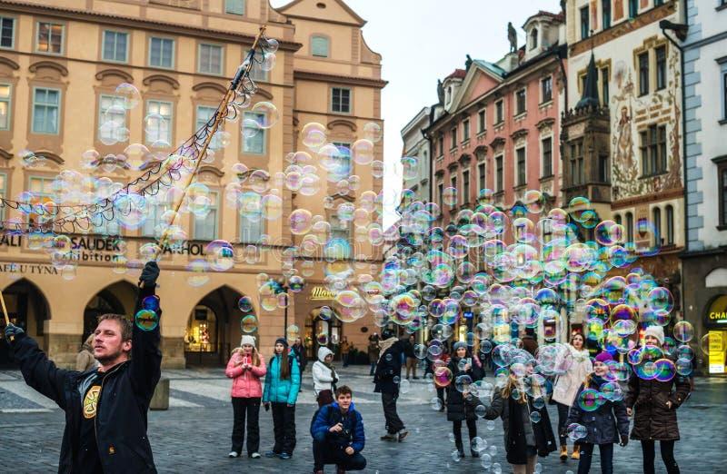 PRAGUE TJECKIEN - JANUARI, 10: Såpbubblor för gatakonstnärdanande i den gamla staden Staromestska kvadrerar i Prague royaltyfria foton