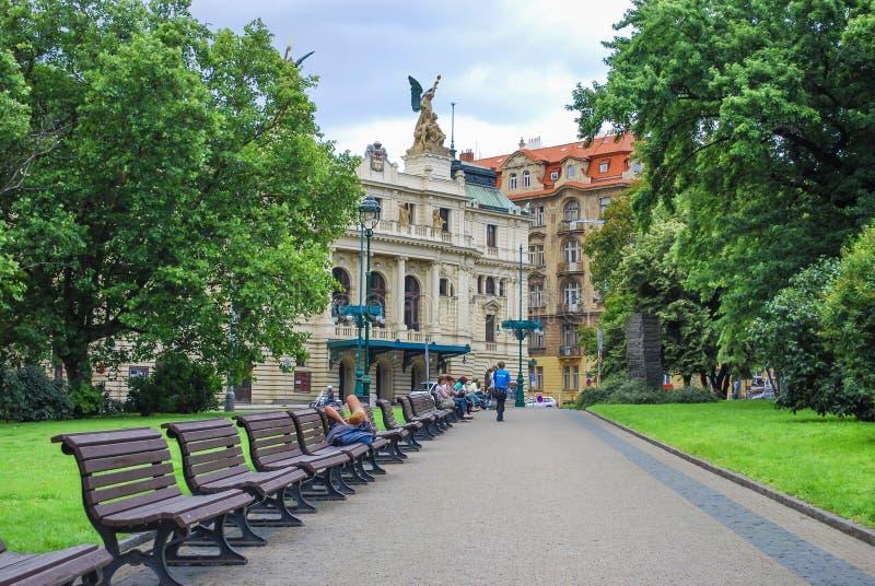 PRAGUE TJECKIEN - JULI 21, 2009 gräsplan parkerar gränden med bänkar med sikten av den dramatiska teatern för den Vinohrady teate arkivbilder