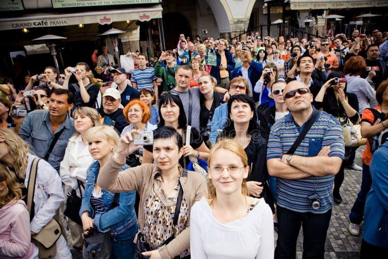 Prague Tjeckien, Maj 2010: En folkmassa av turister ser upp till den gamla astronomiska klockan royaltyfria foton