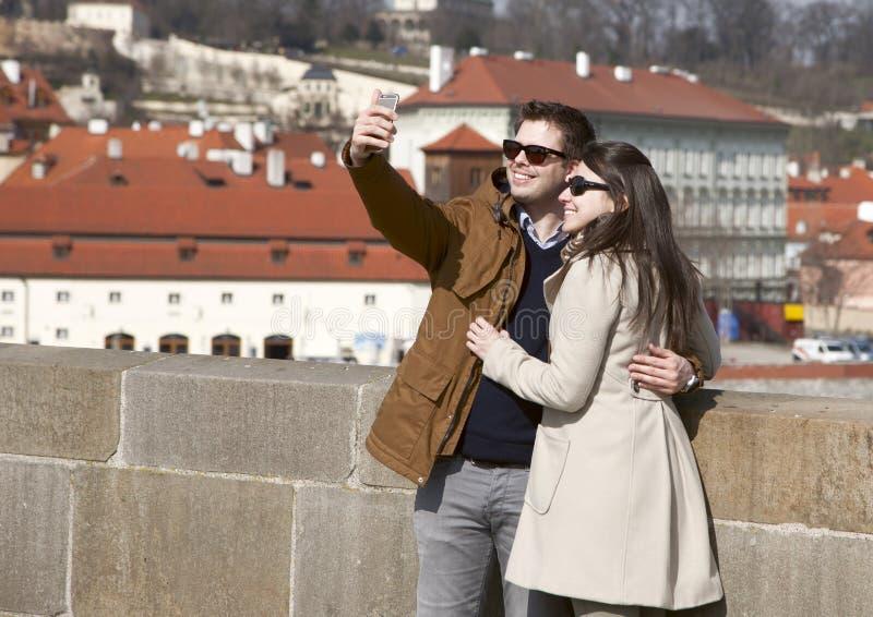 Prague Tjeckien - mars 13, 2017: För tagandeselfie för lyckliga unga par gör den förälskade ståenden på de nätta turisterna för g arkivbilder